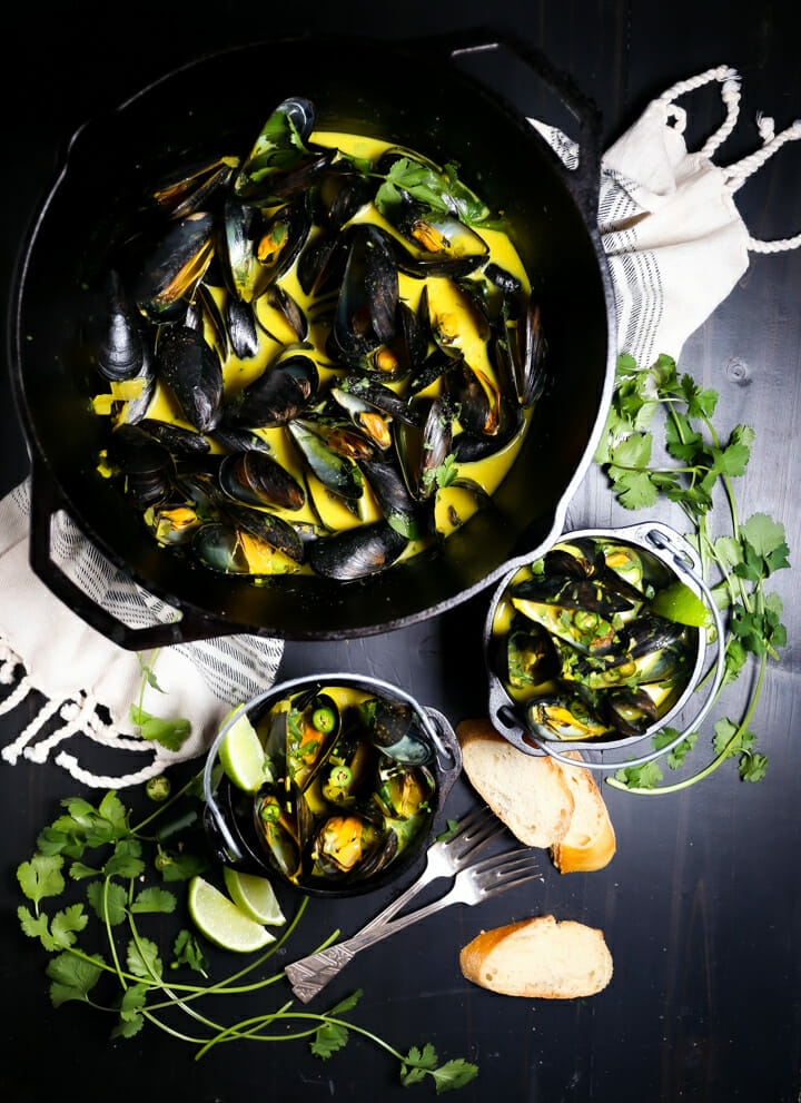 Two servings of Curry Coconut Mussels in back crocks with a pot of mussels on a towel.