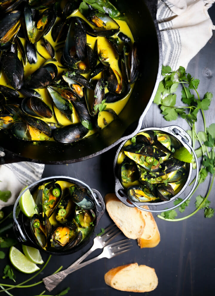 Two servings of Curry Coconut Mussels with sliced bread for dipping.