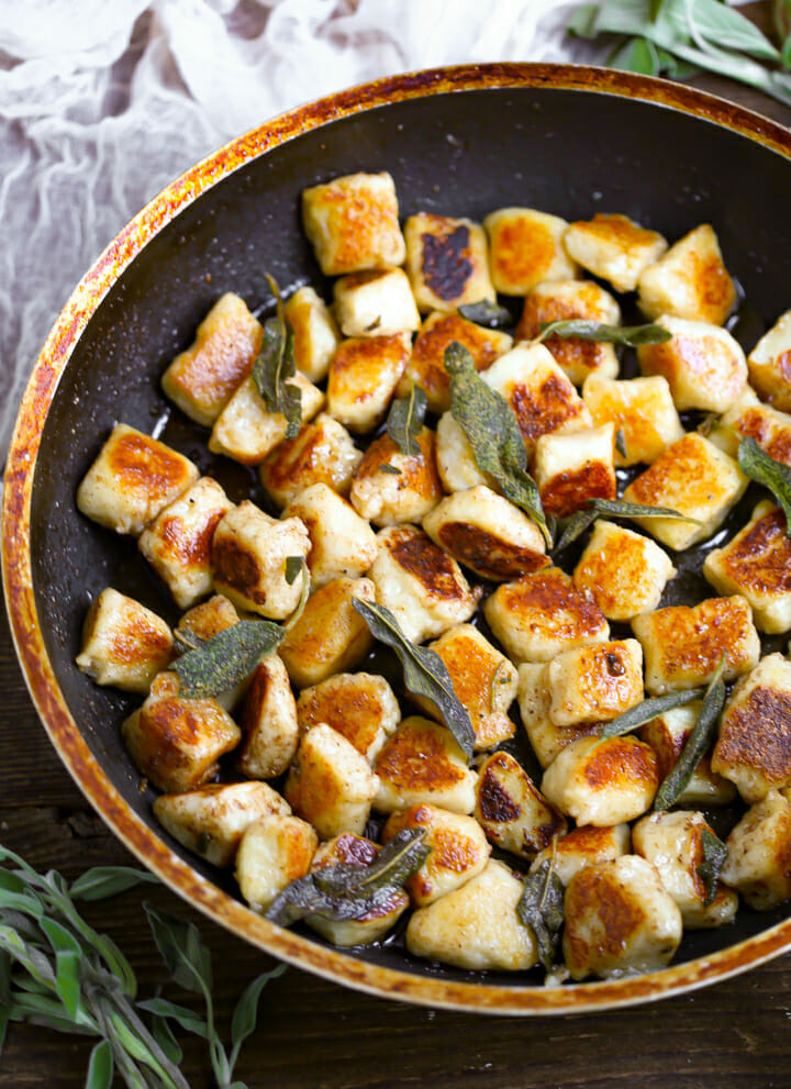 Pan Seared Gnocchi in a pan topped wit frizzled sage leaves.
