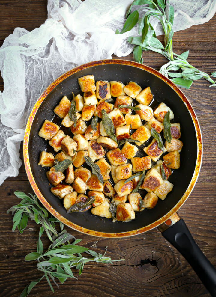 Pan Seared Gnocchi in Brown Butter Sage Sauce in a pan with fresh sage scattered around.