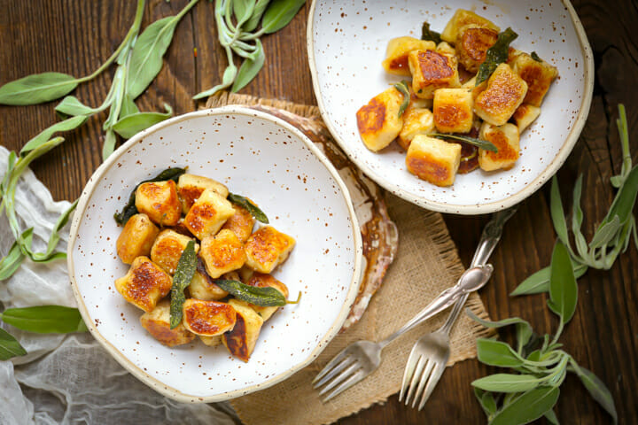 Two servings of pan seared gnocchi in bowls with forks and fresh sage.
