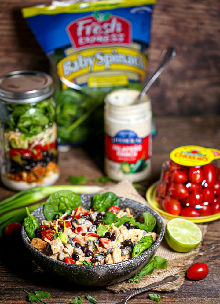 Layered Mexican Salad in a Jar in a serving bowl with all of the ingredients scattered around on the table.