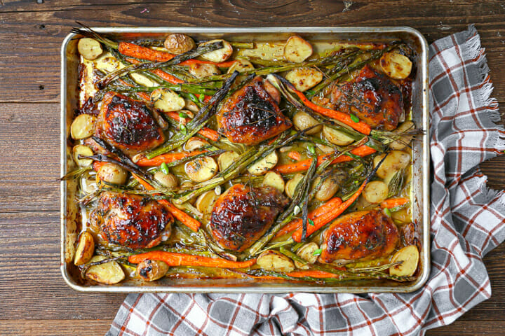 Overhead view of mustard glazed chicken on an sheet pan with roasted vegetables.
