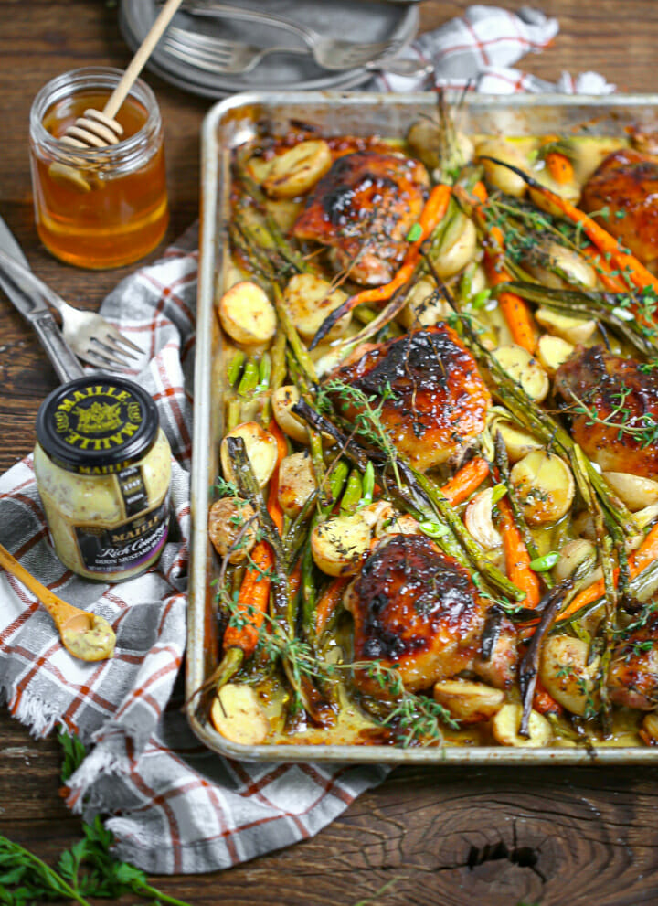 A jar of Maille mustard next to oven roasted sheet pan chicken.