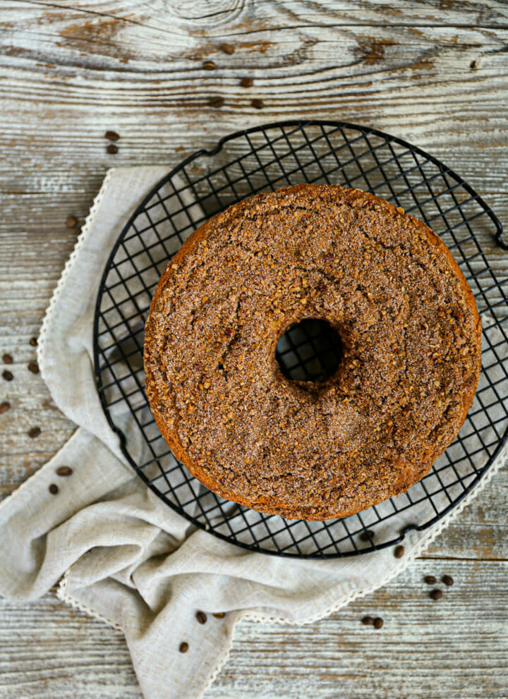 Sour Cream Coffee Cake on a round wire cooling rack with coffee beans scattered around.