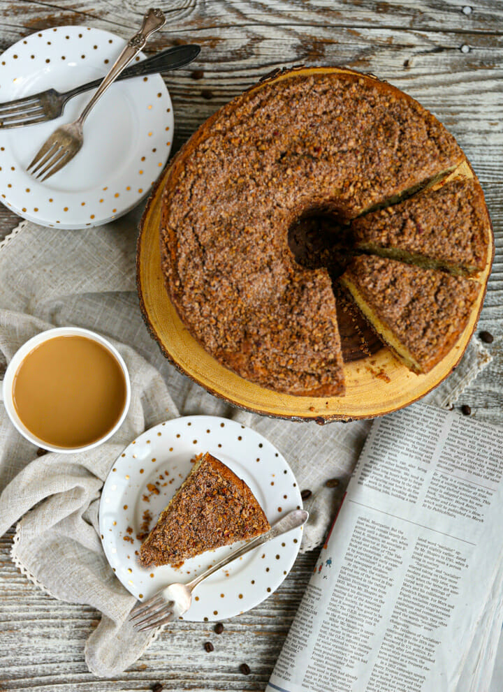 An overhead shot of Sour Cream Coffee Cake on a round wood plate next to a slice and cup of coffee.