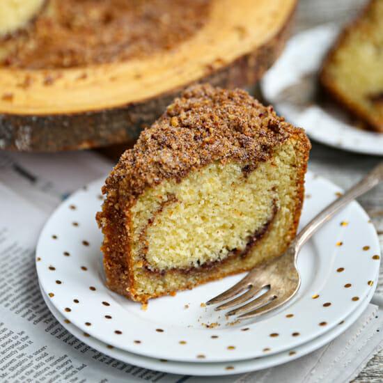 A slice of Sour Cream Coffee Cake on a polka dot plate.