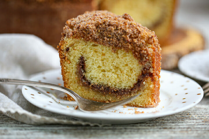 A close up of a slice of Sour Cream Coffee Cake with a pecan cinnamon swirl.