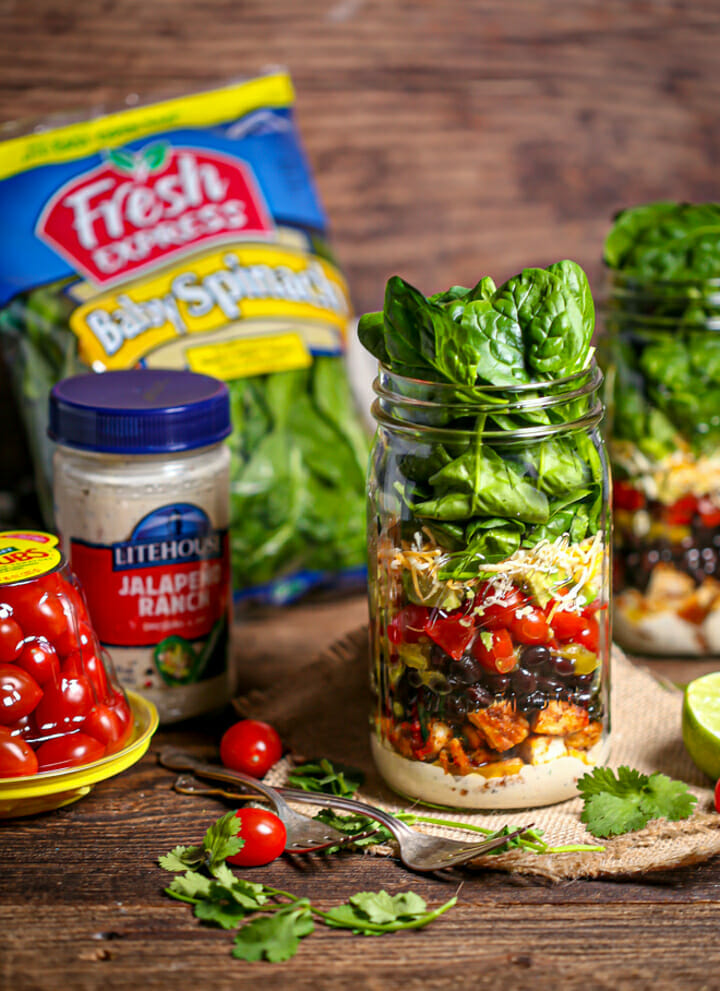 Layered Mexican Salad in a Jar with spinach, tomatoes and dressing on the table.